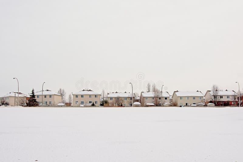 Snö täckte fältet och rad av förorts- hus i Gatineau royaltyfri fotografi