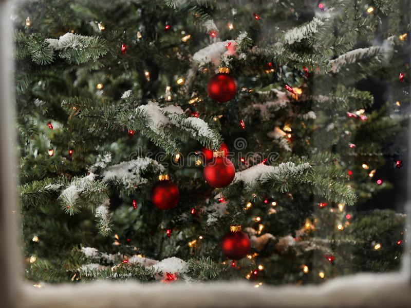Snö täckte fönstret med julgranen och glödande ljus royaltyfria foton