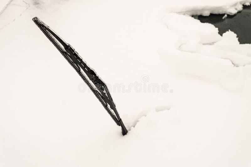Snö täckte främre bilfönsterexponeringsglas Iskall сar torkare som klibbar ut ur snö royaltyfria foton