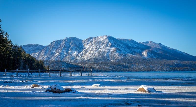 Snö täckte stranden och berg på Lake Tahoe, Kalifornien royaltyfria foton