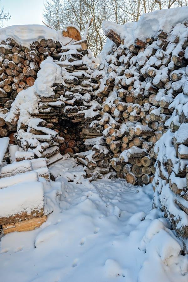 Snö täckte vedträbuntar arkivbilder