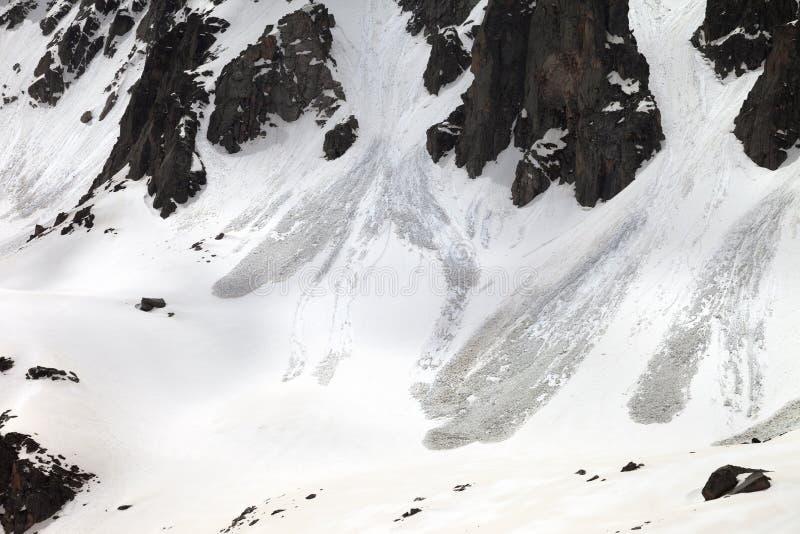 Snöa berget med spår från lavin i vårdag fotografering för bildbyråer