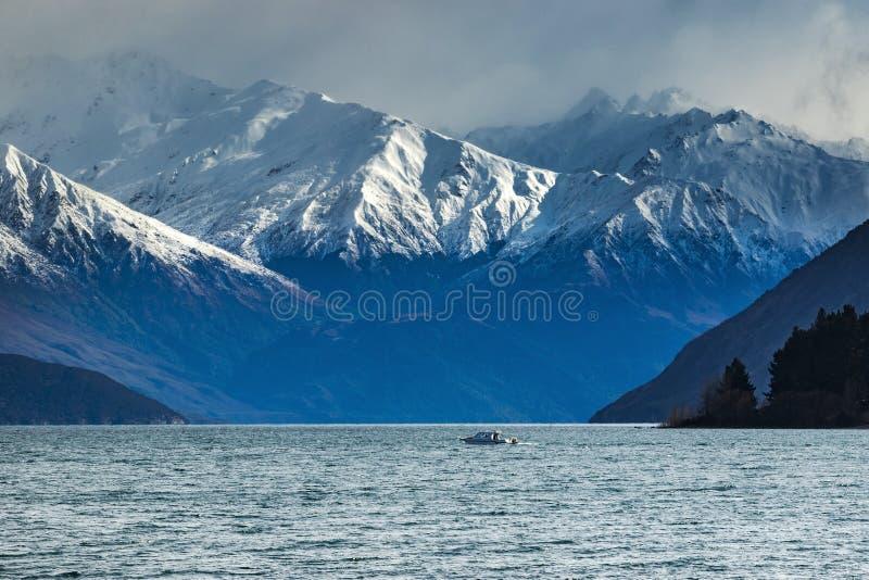 Snöa bergplatsen och det motoriska fartyget över sjöwanakaen härlig de royaltyfria foton