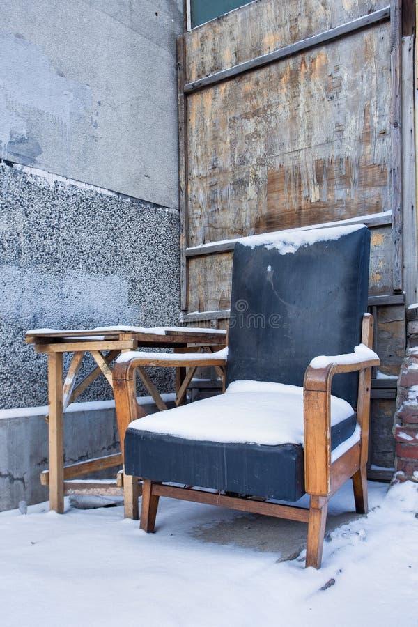 Snöa den dolda gamla fåtöljen i en murken miljö, Changchun, Kina arkivbilder