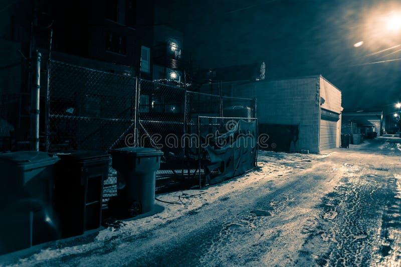 Snöa den dolda mörka stads- stadsgränden i vintern på natten arkivfoton