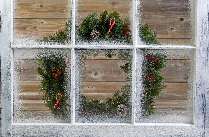 Snöa det dolda fönstret med den dekorativa julkransen på fönster royaltyfri foto
