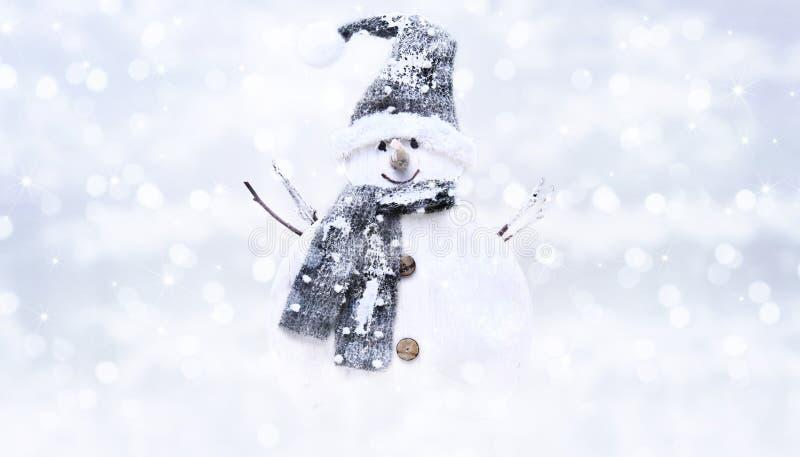 Snöa mannen på suddig ljus bakgrund för julljus som hälsar arkivbild