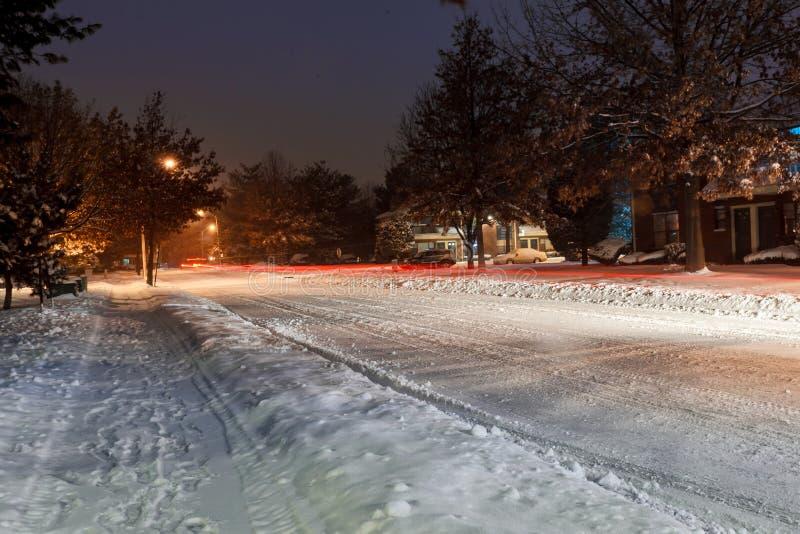 Snöa på gatan och huvudvägen under December 2016, iskall vägvinterstorm, i stadsområde på natten royaltyfri bild