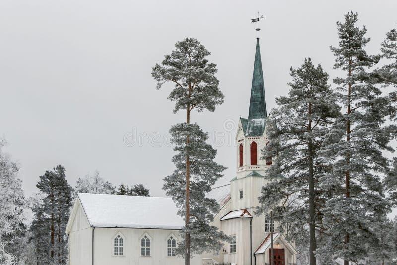 Snöa på nordisk kyrka i skog på vintern royaltyfri foto