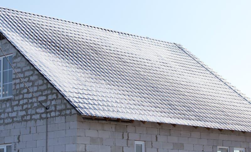 Snöa på taket av huset i vinter royaltyfri bild