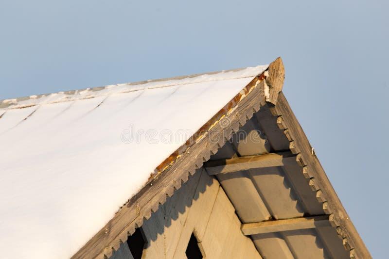 Snöa på taket av huset på solnedgången royaltyfria foton