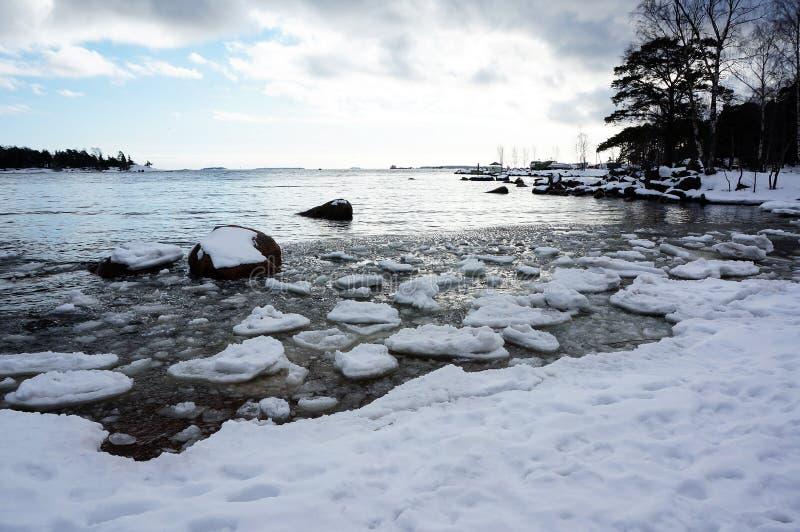 Snöa täckte stranden och isen i havet royaltyfri foto