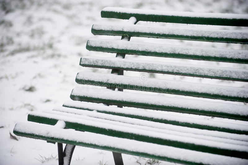 Snöad träbänk royaltyfria foton