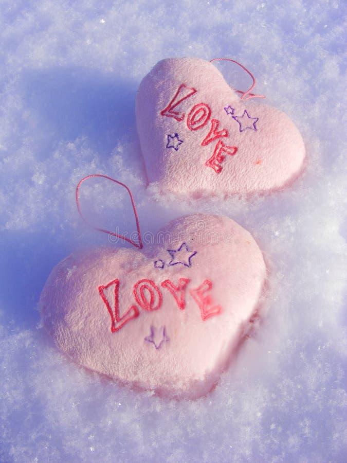 Snöbakgrund med förälskelse för två rosa hjärtor fotografering för bildbyråer