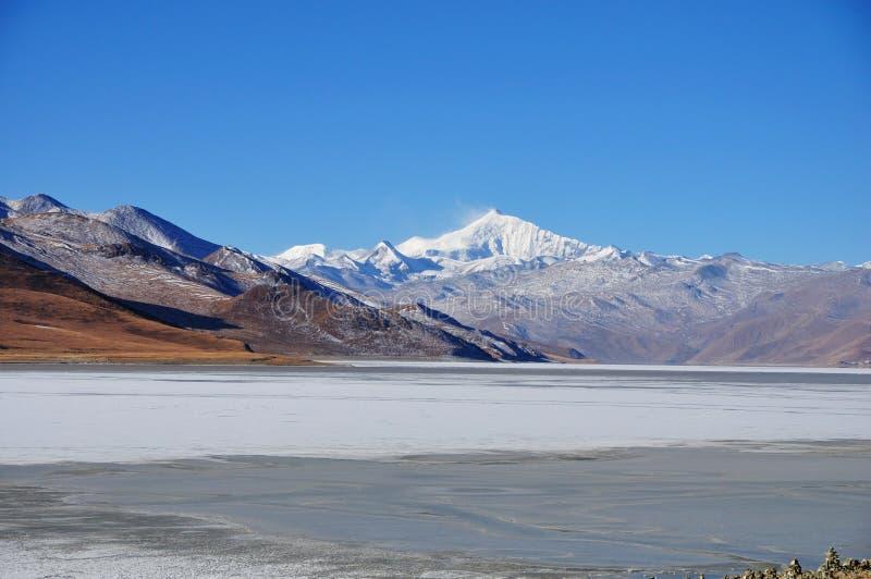 Snöberg och djupfryst sjö arkivfoto