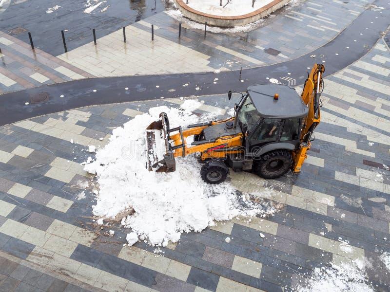 Snöborttagning förbi traktoren från stadsgatan fotografering för bildbyråer