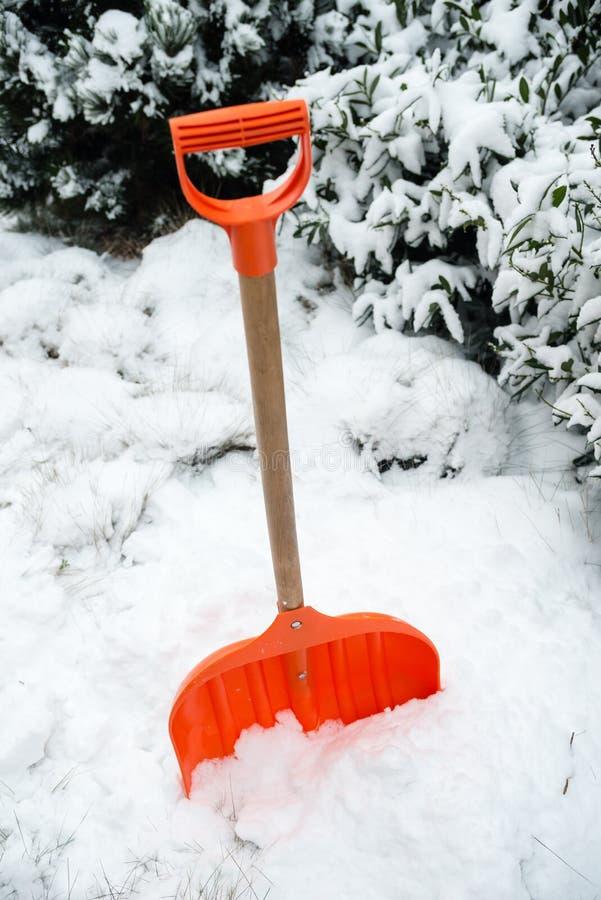 Snöborttagning Orange skyffel i snö fotografering för bildbyråer