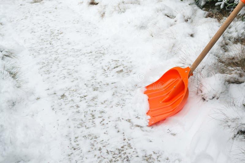 Snöborttagning Orange skyffel i snö arkivbilder