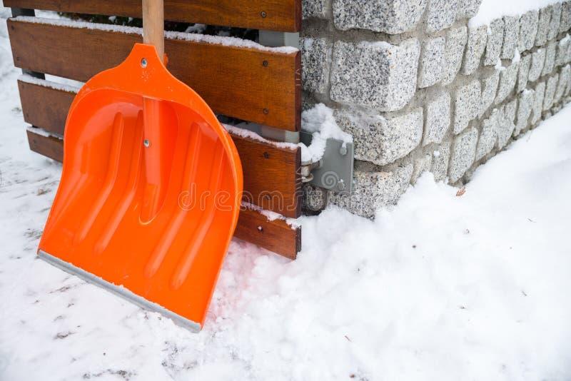 Snöborttagning Orange skyffel i snö royaltyfri fotografi