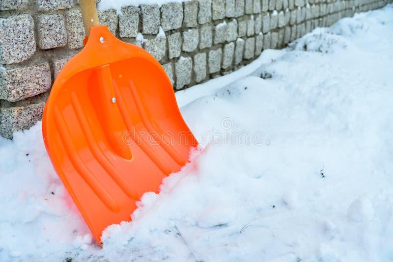 Snöborttagning Orange skyffel i snö royaltyfri foto
