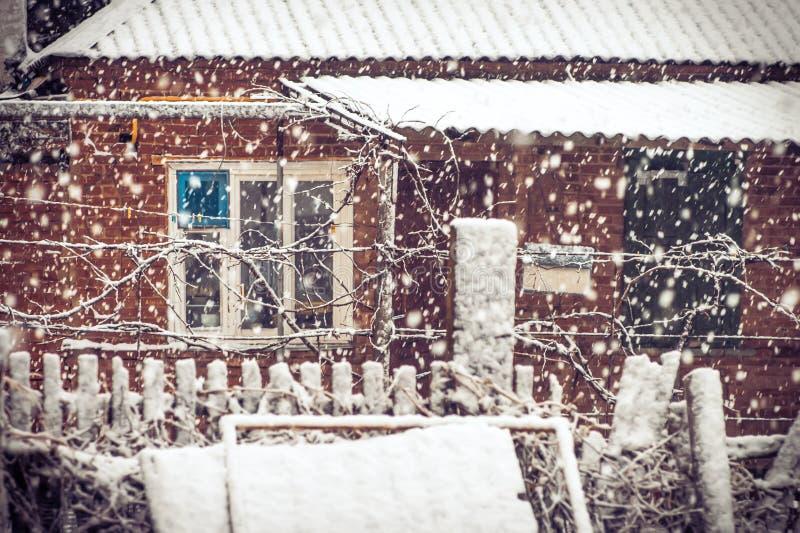 Snöfallvinterväder i by med snöflingor och det gamla husfönstret royaltyfria foton