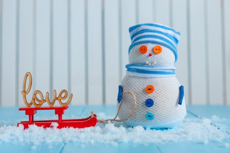 Snögubbe som tycker om en släderitt med ordet FÖRÄLSKELSE royaltyfri foto
