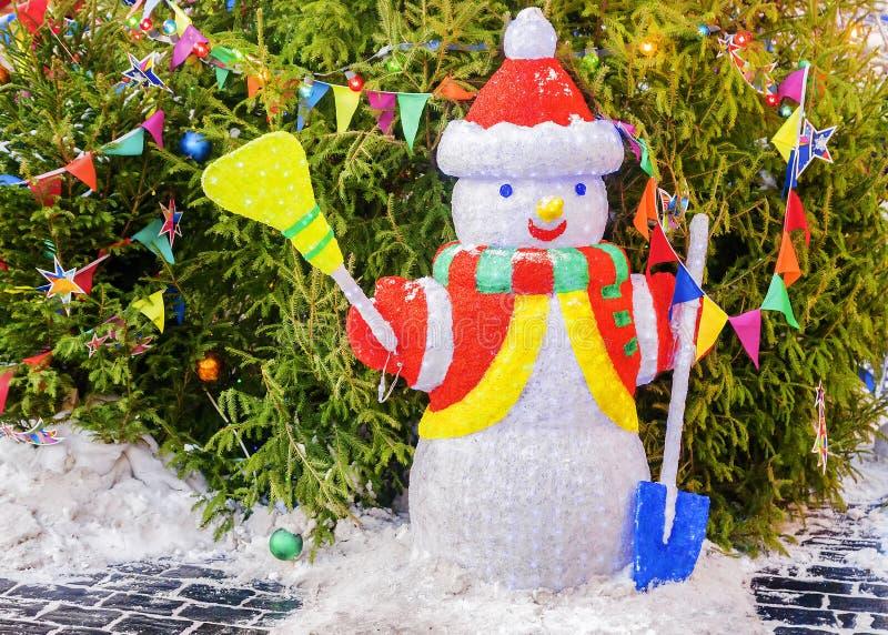 Snögubbe under träd med leksakprydnader och ljus arkivfoton