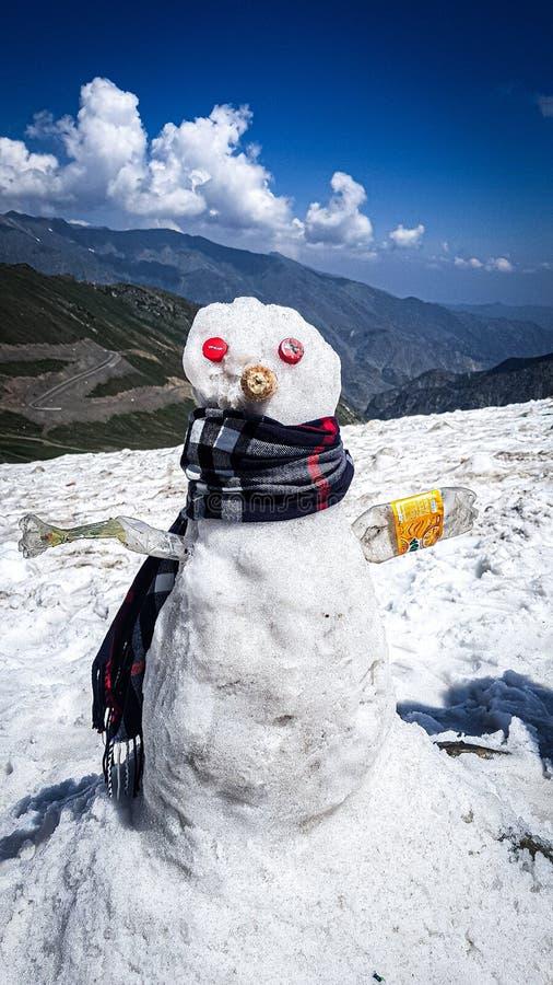 Snögubbeanseende på bärande mufler för is med hans händer som utgöras av den plast- flaskan och ögon som utgöras av kapsyler arkivfoton