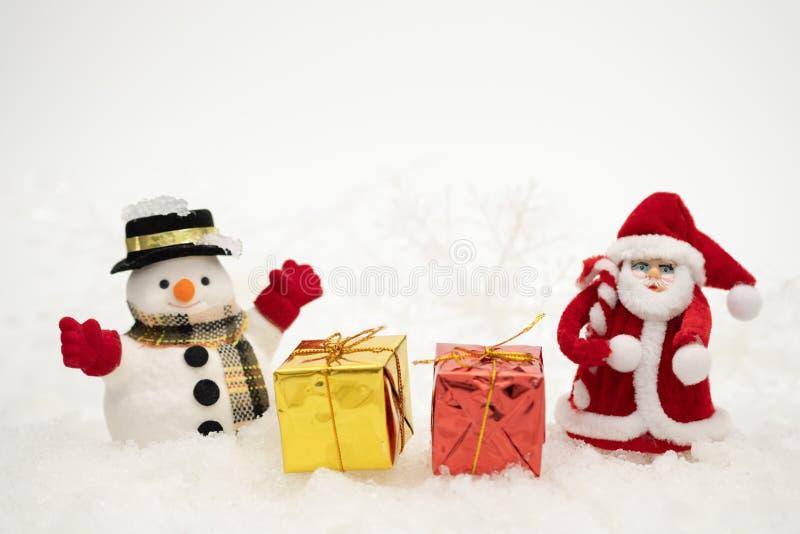 Snögubben med gåvaasken står i snöfall, begrepp för glad jul och för lyckligt nytt år arkivfoto
