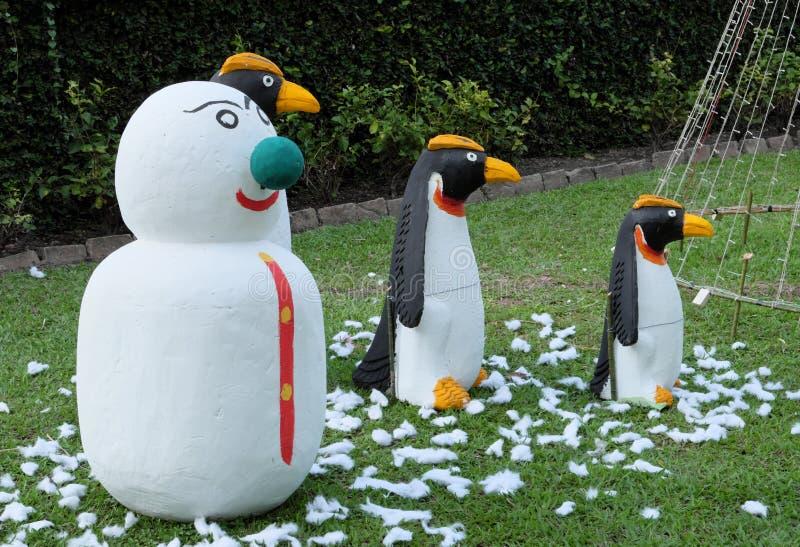 Snögubben och tre pingvin på en grön gräsmatta, arbeta i trädgården skulptur arkivbild
