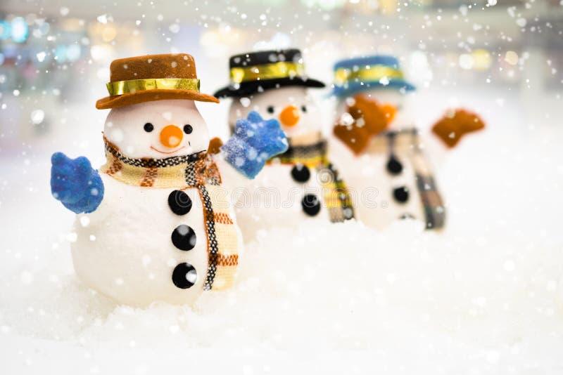 Snögubben står i snöfall, begrepp för glad jul och för lyckligt nytt år arkivbilder