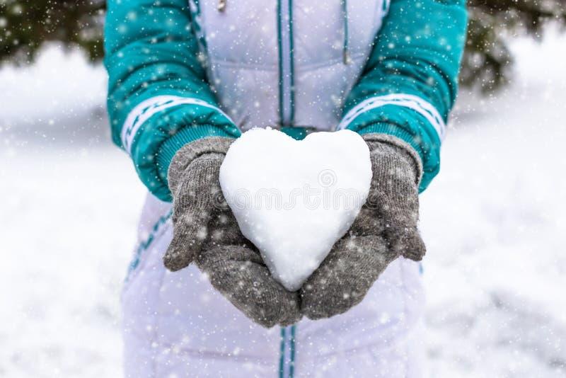 Snöhjärta i kvinnas heand Vinterromantikerbegrepp royaltyfri foto