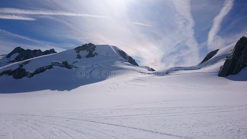 Snöig berg i solen royaltyfri foto