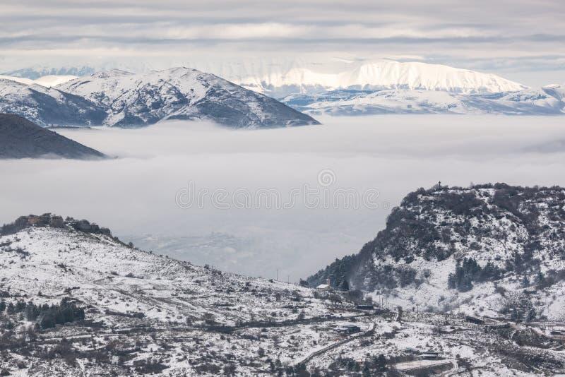 Snöig berg med dimma arkivfoton