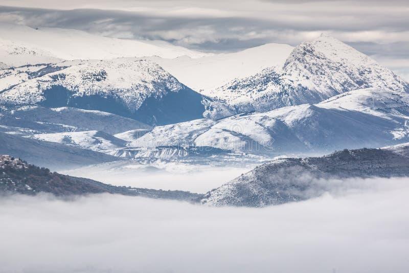 Snöig berg med dimma arkivbilder
