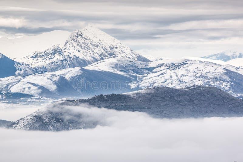 Snöig berg med dimma royaltyfria foton