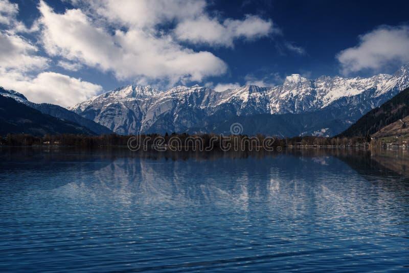 Snöig berg som reflekterar i en sjö royaltyfri foto