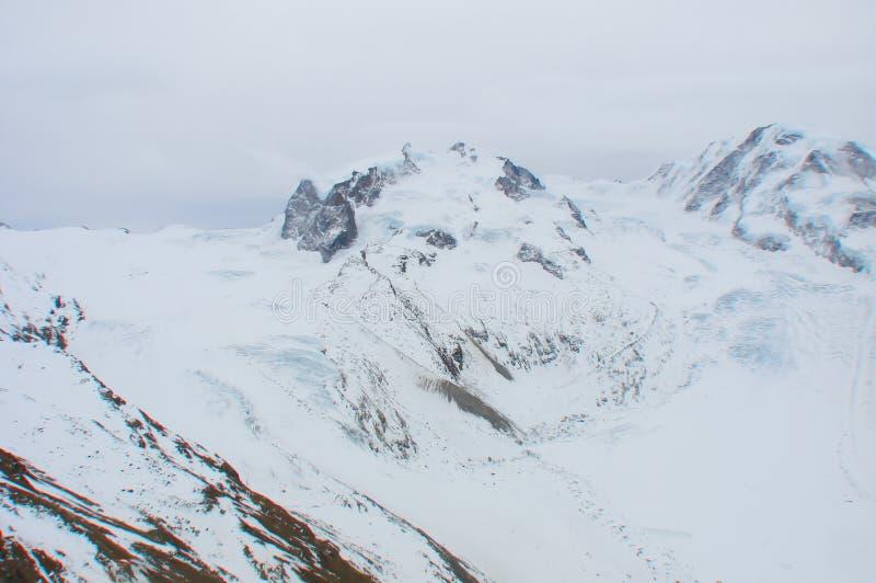 Snöig bergkant med glidning av glaciären i schweiziska fjällängar arkivbild