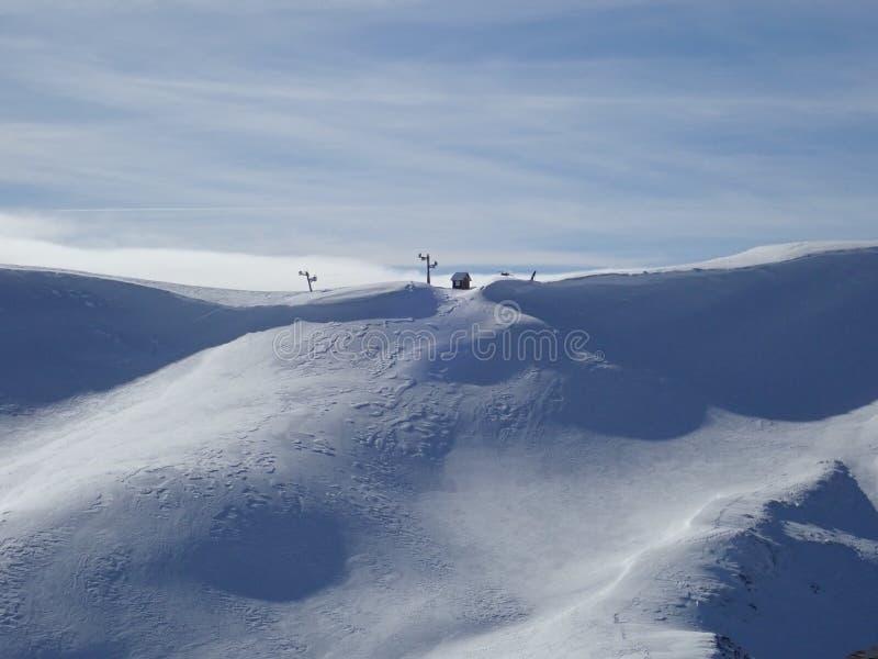 Snöig berglutning med skidlift arkivbild