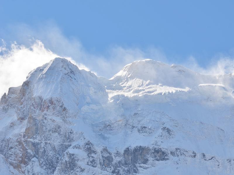 Snöig bergmaximum som är fullt med snölandskap i klar blå himmel royaltyfri fotografi