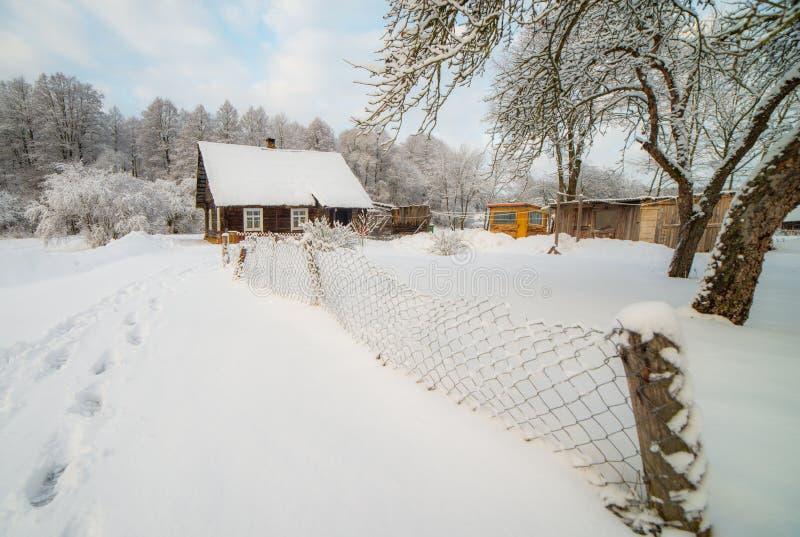 Snöig bygd av små trähus nära skog royaltyfria foton