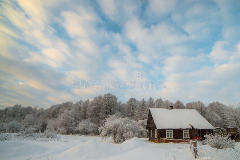 Snöig bygd av små trähus nära skog arkivbilder