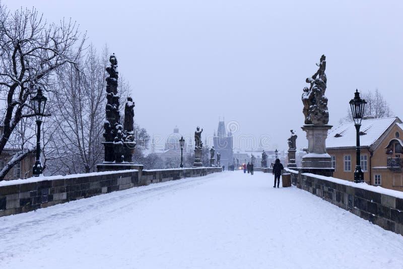 Snöig dimmig Prague gammal stad med brotornet och St Francis av den Assisi domkyrkan från Charles Bridge med dess barocka statyer royaltyfria foton