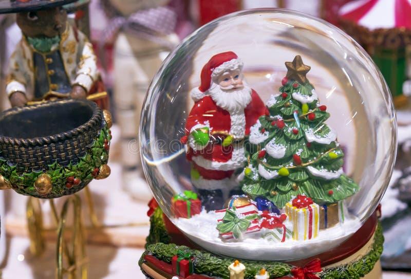 Snöig exponeringsglasboll med Santa Claus och julträdet inom royaltyfri fotografi