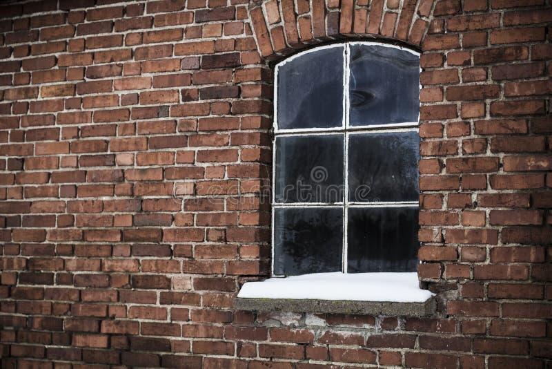 Snöig fönster för tappning, tegelstenvägg arkivfoto