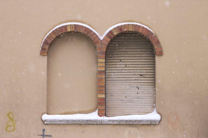 Snöig fönster med den runda tegelstenbågen fotografering för bildbyråer
