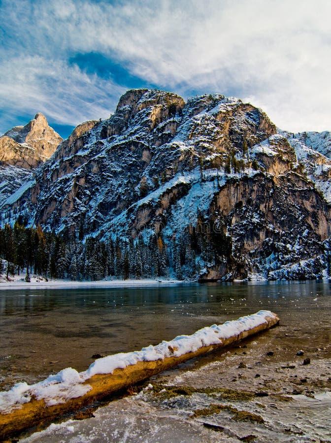 Snöig inloggningsbergsjö med berg och blå himmel royaltyfri fotografi