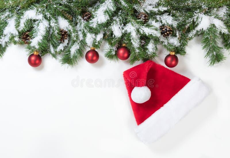 Snöig jul förgrena sig med den Santa Claus hatten och röda prydnader royaltyfria foton