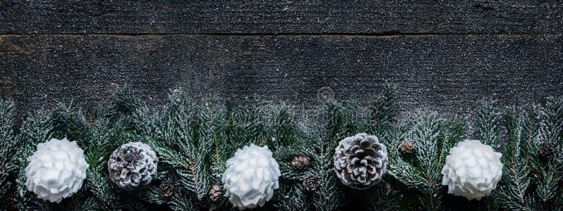 Snöig julbakgrund, granträdfilialer med sörjer kottar och Xmas-struntsaker på träbakgrund arkivfoton