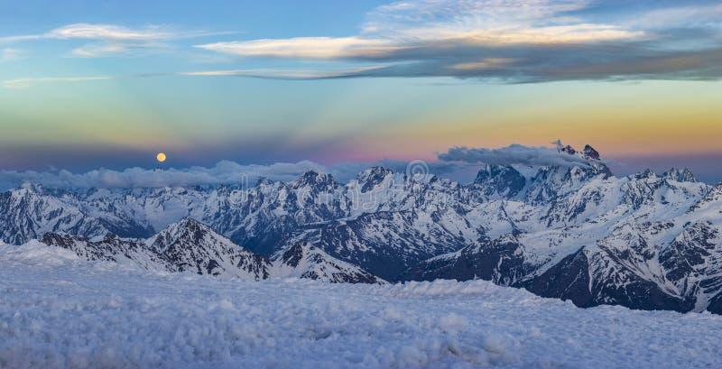 Snöig Kaukasus berg på solnedgången med moonrising och Anticrepuscular strålar arkivfoto